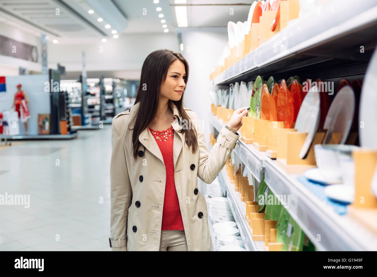 Beautiful woman shopping tableware in supermarket - Stock Image