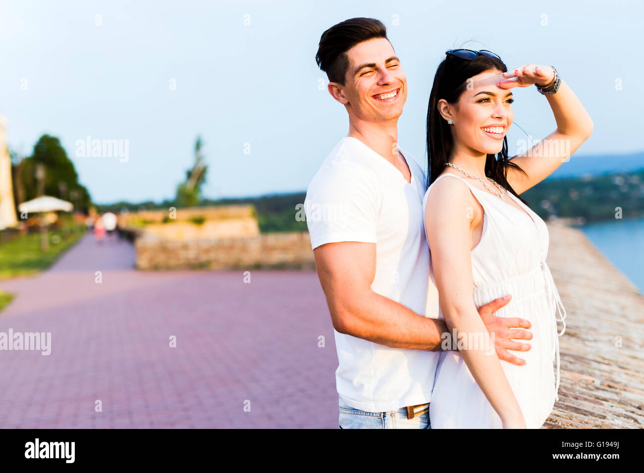 Beautiful couple in love watching sunset - Stock Image