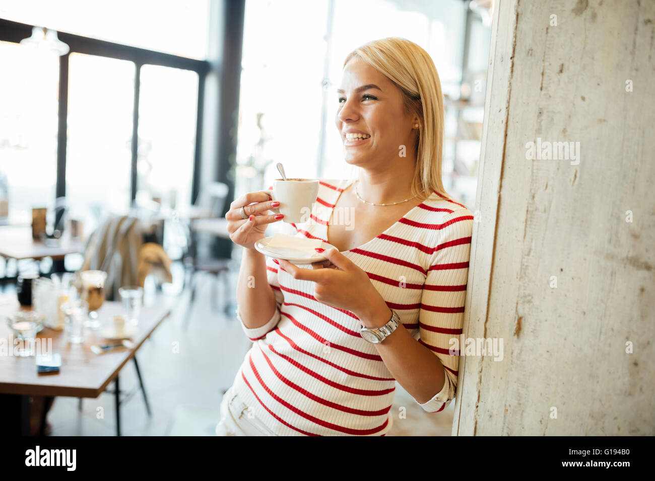 Portrait of a beautiful woman drinking coffee, tea in a cafe - Stock Image