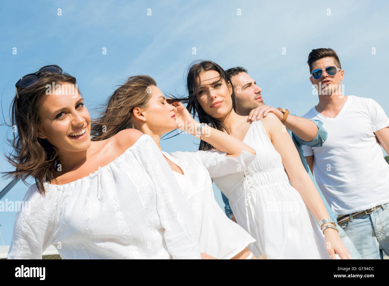 Young people on the beach posing with wind blowing their hair - Stock Image