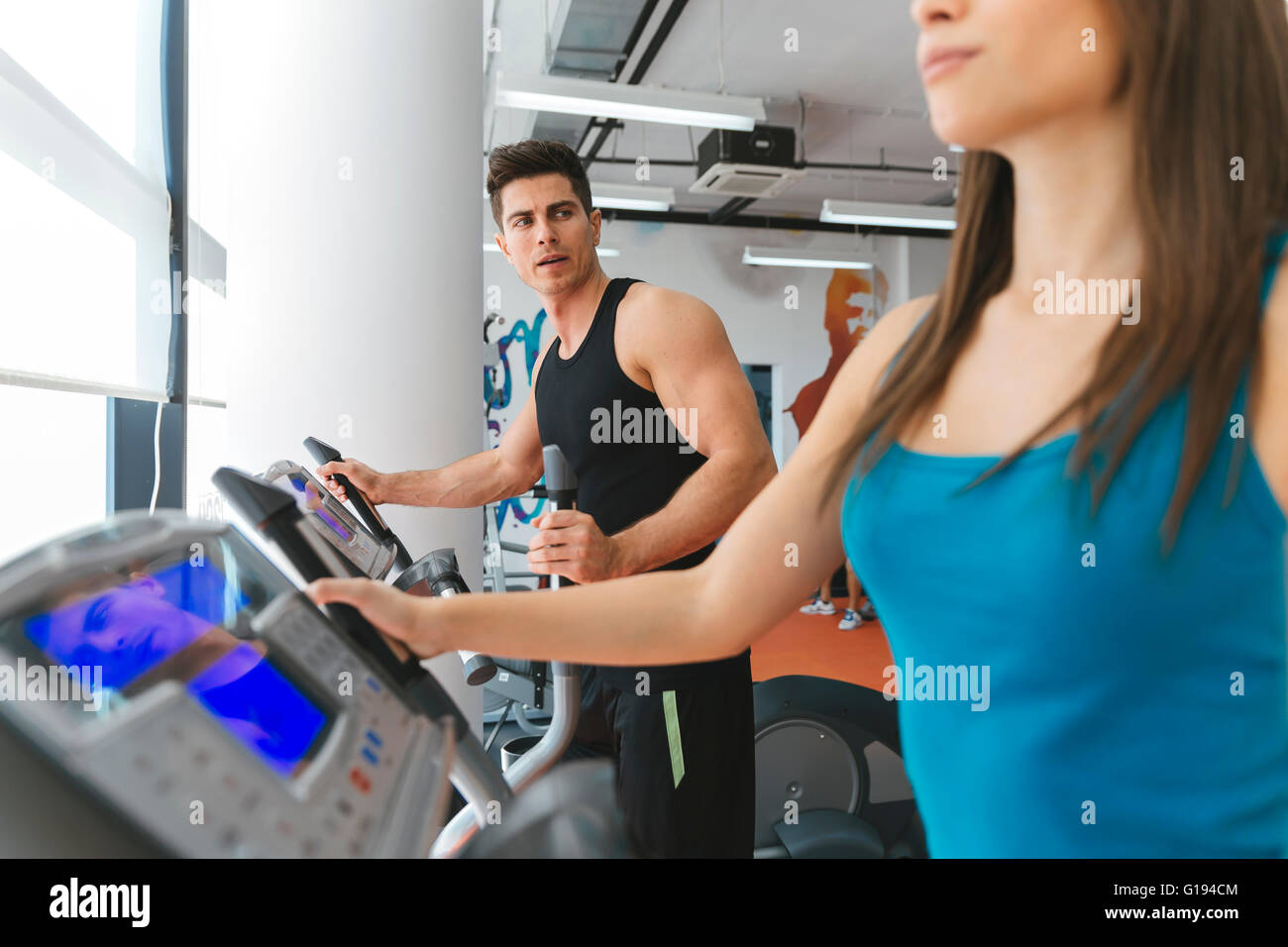 People exercising in gym to keep body in shape - Stock Image