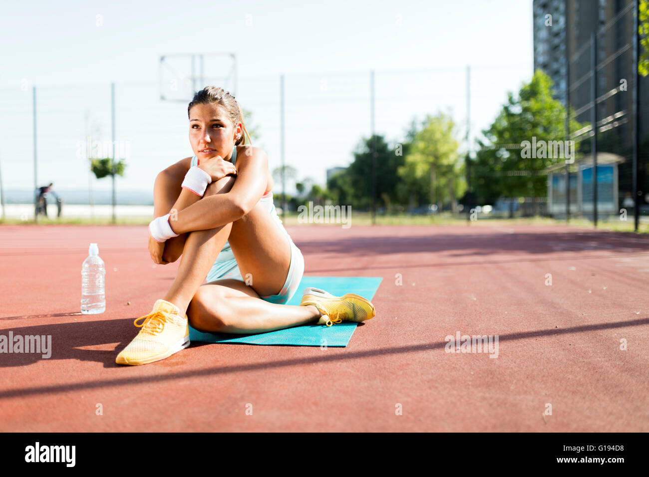 Portrait of a young beautiful fit sportswoman in the city taking a break - Stock Image