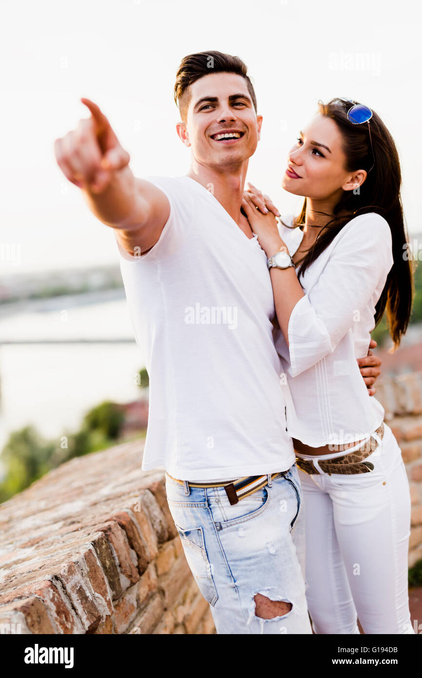 Happy couple pointing in a direction  and smiling - Stock Image