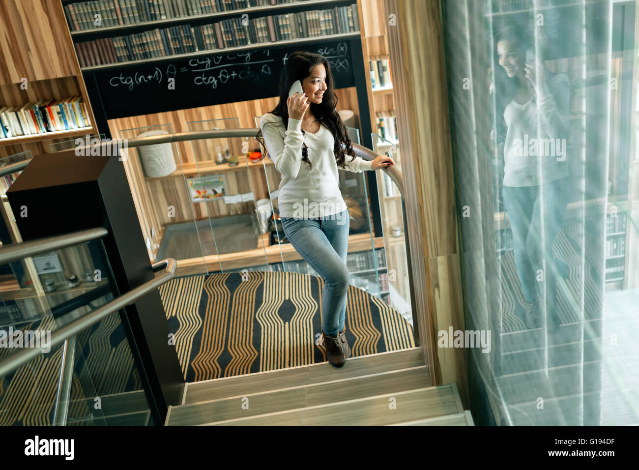 Businesswoman using phone indoors and smiling - Stock Image