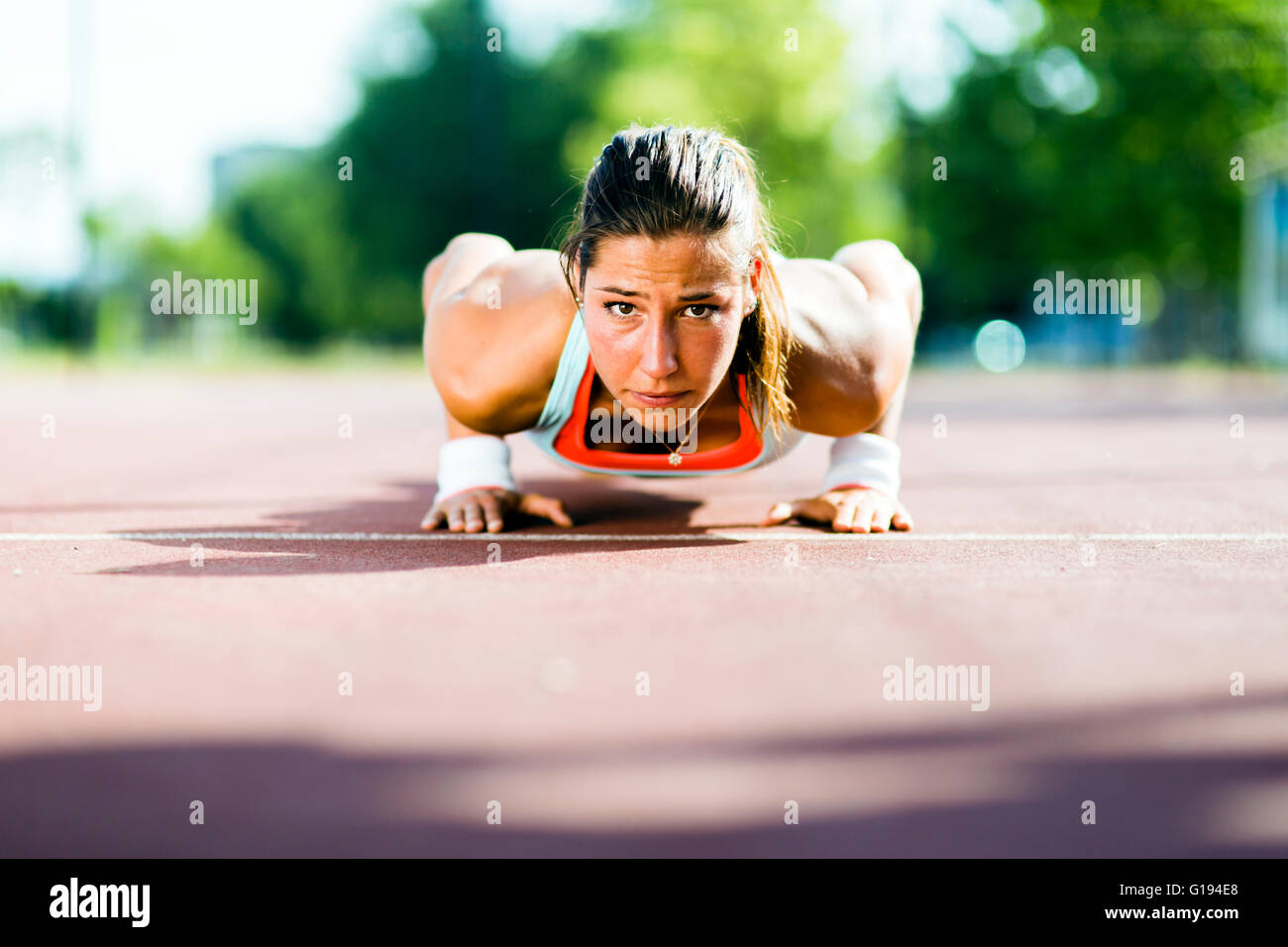Focused young beautiful woman doing push-ups outdoors on a hot summer day - Stock Image