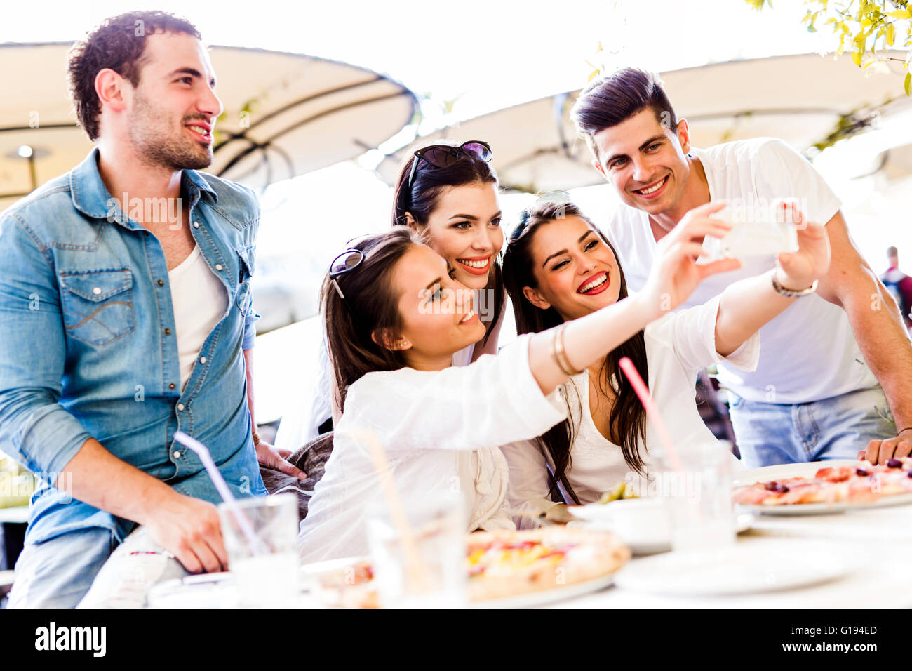 Group of young beautiful people sitting in a restaurant and taking a selfie while smiling - Stock Image