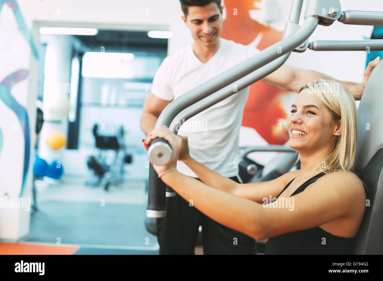 Beautiful woman exercising in gym with some help by personal trainer Stock Photo