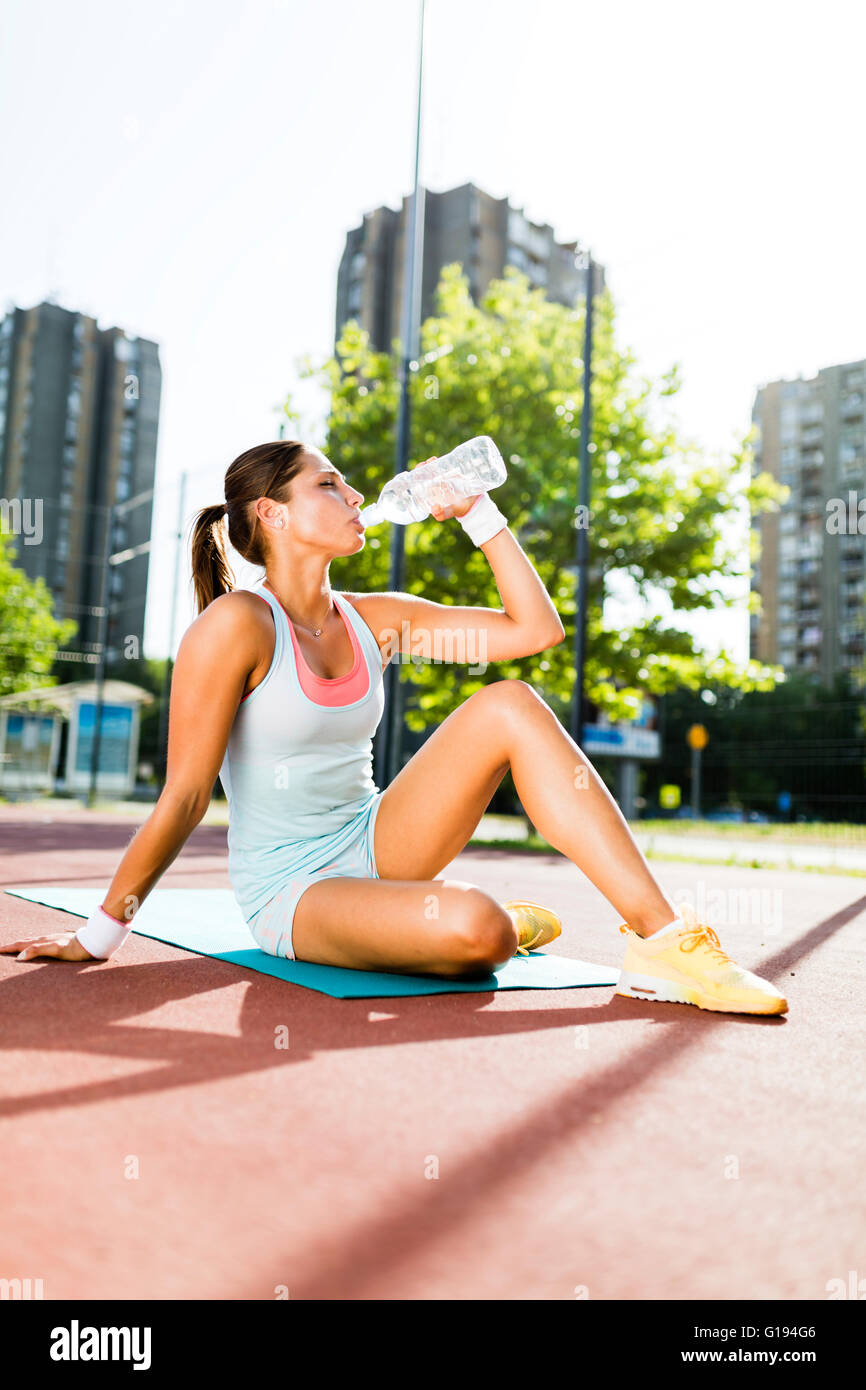 Young beautiful woman drinking water after exercise in a city training court on a sunny day - Stock Image