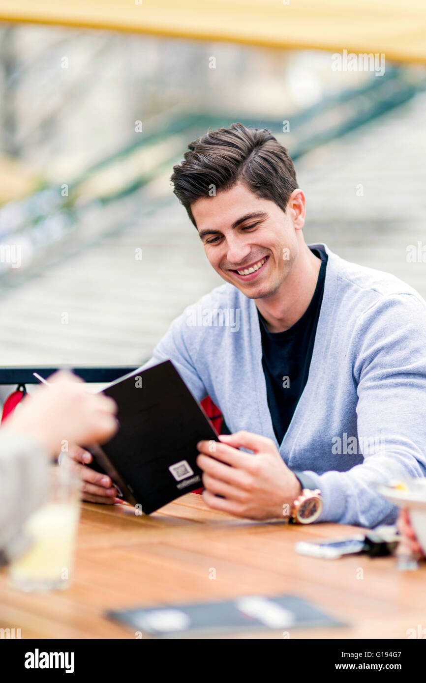 Young handsome man looking at the menu outdoors - Stock Image