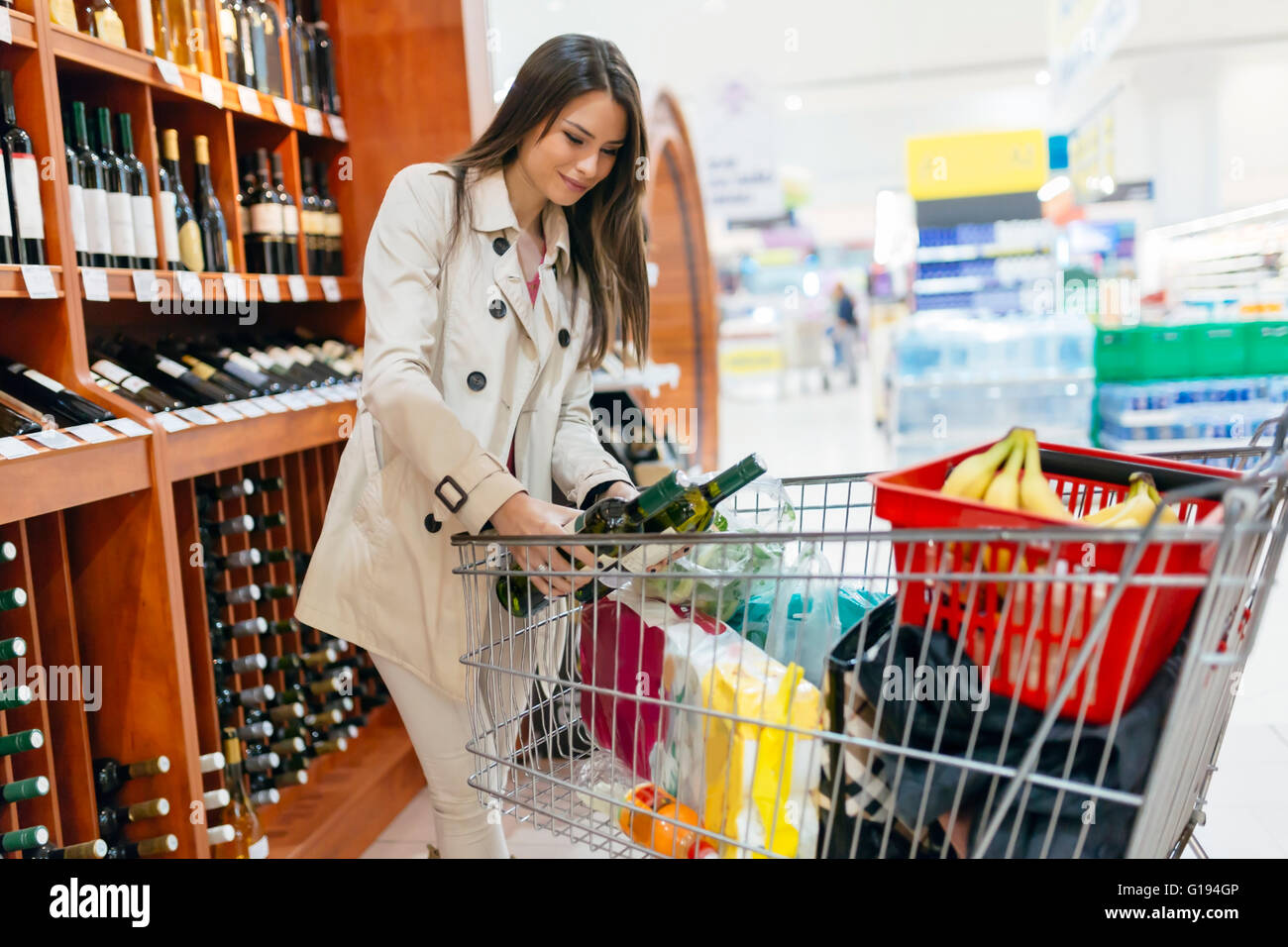 Beautiful woman buying wines in supermarket - Stock Image