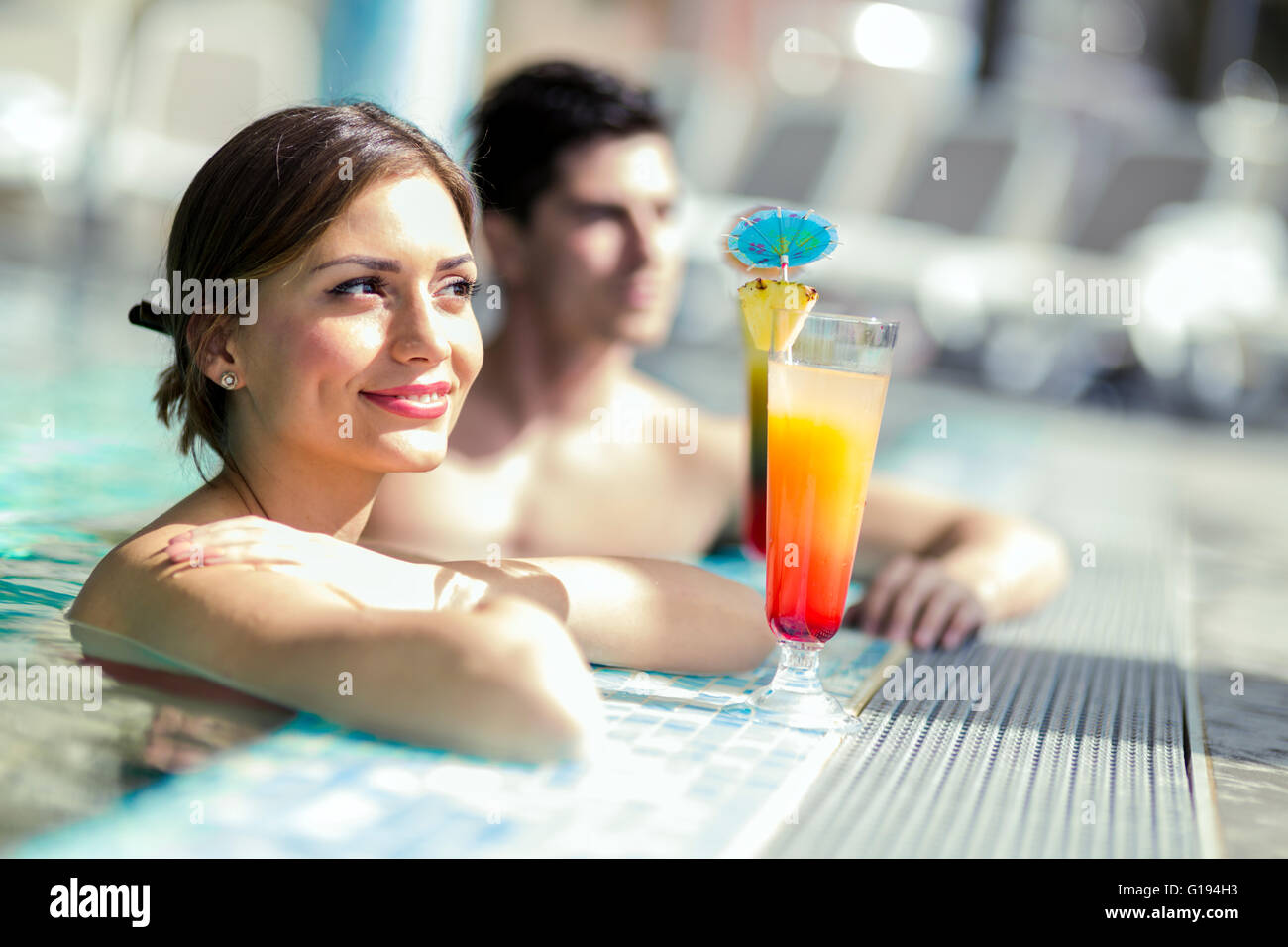 Young people drinking cocktails by the swimming pool and relaxing - Stock Image