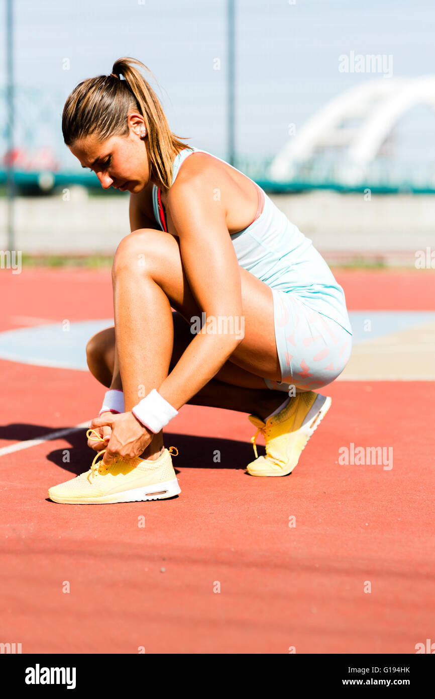 Athlete tying shoe lace with both hands in summer - Stock Image