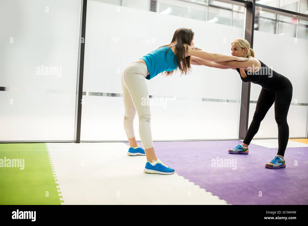 Beautiful women stretching and exercising in fitness club - Stock Image