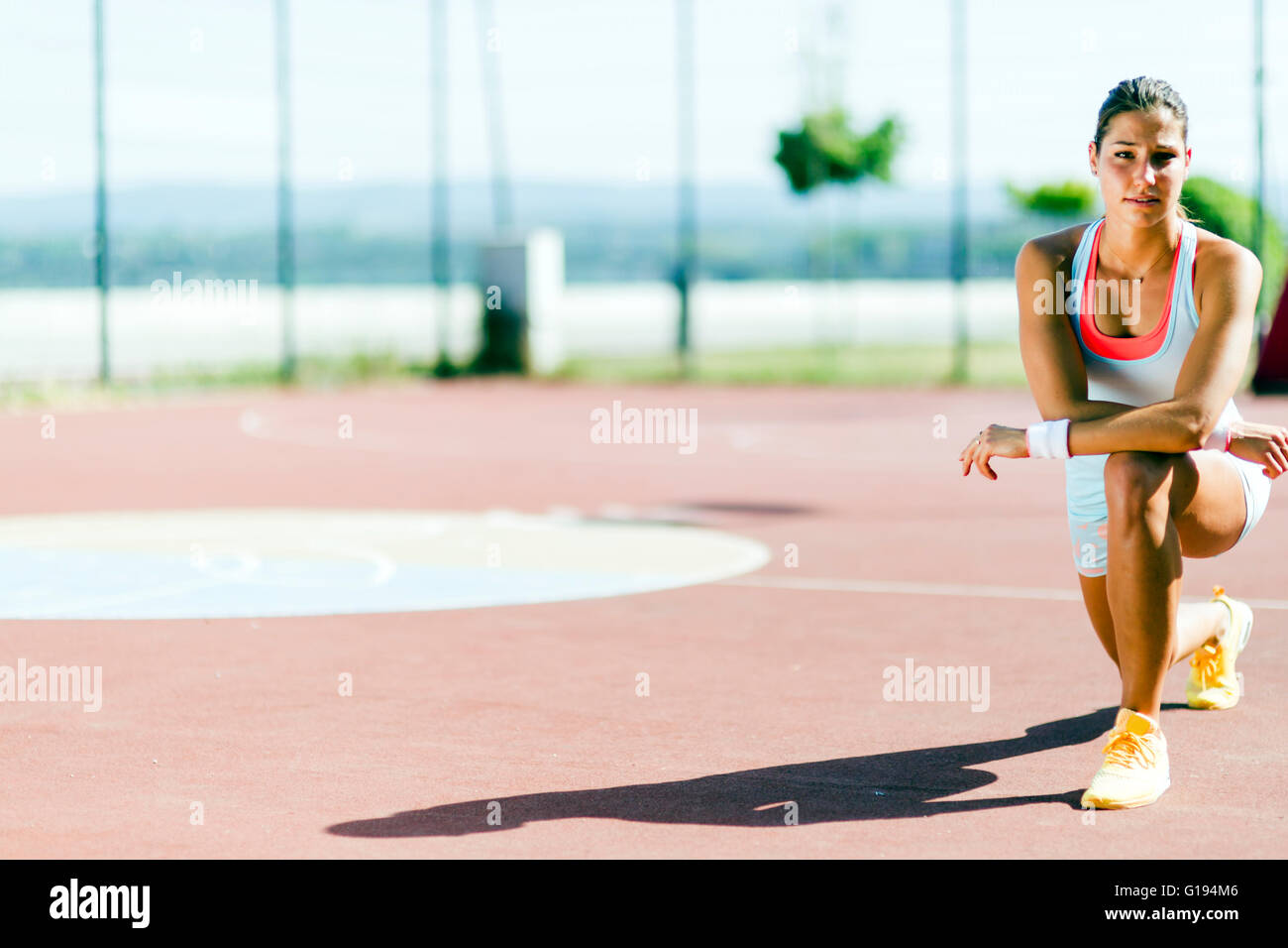 Portrait of a young beautiful fit woman outdoors stretching - Stock Image