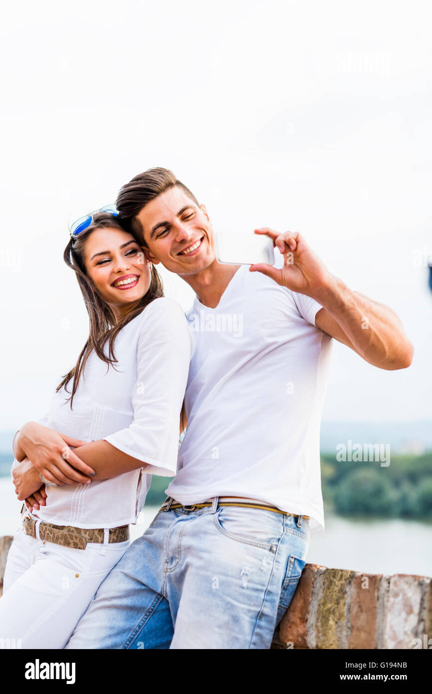 Young beautiful couple taking a selfie of themselves and being happy - Stock Image