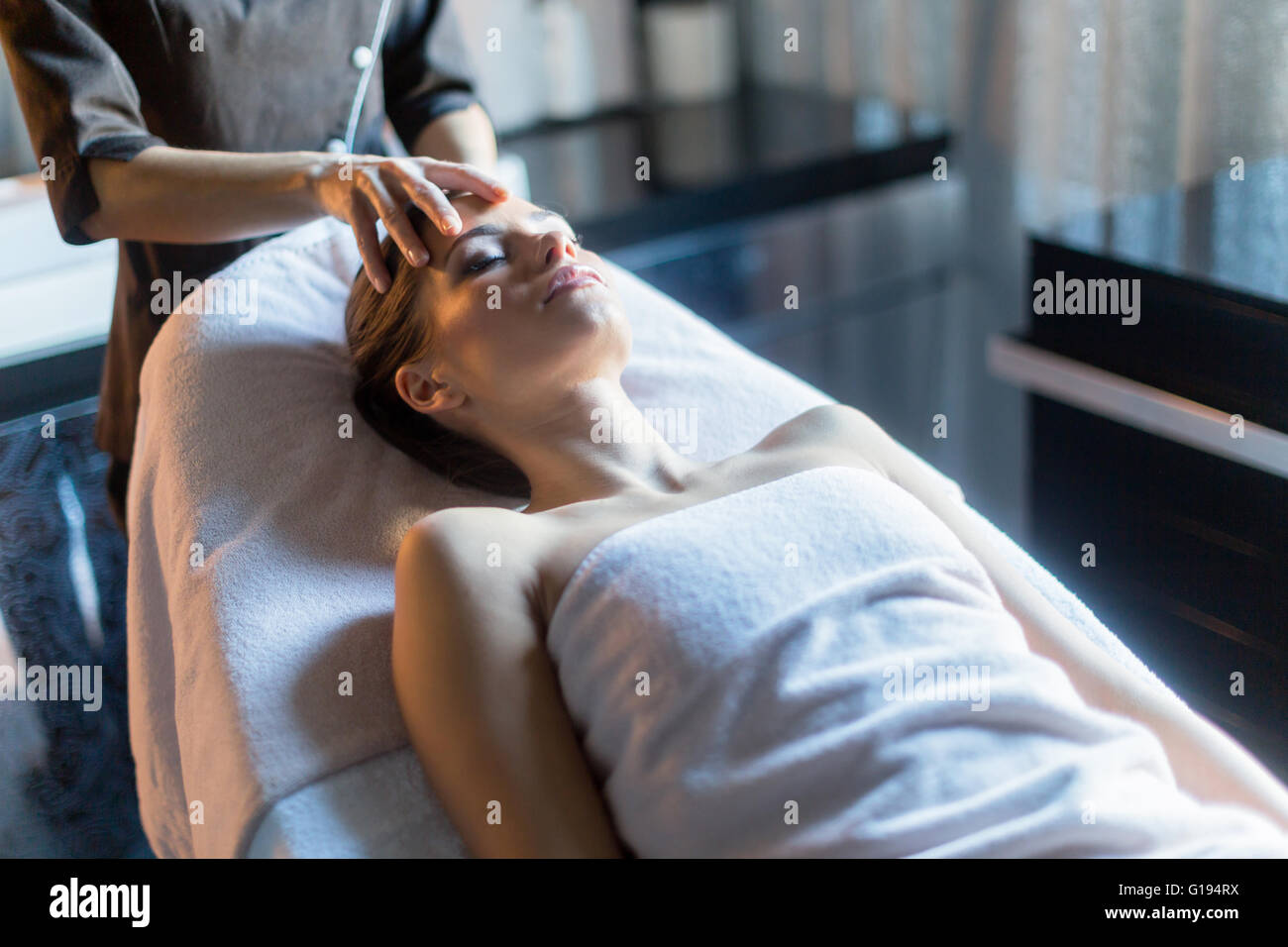Masseur treating face of a beautiful, young woman lying on the massage table - Stock Image