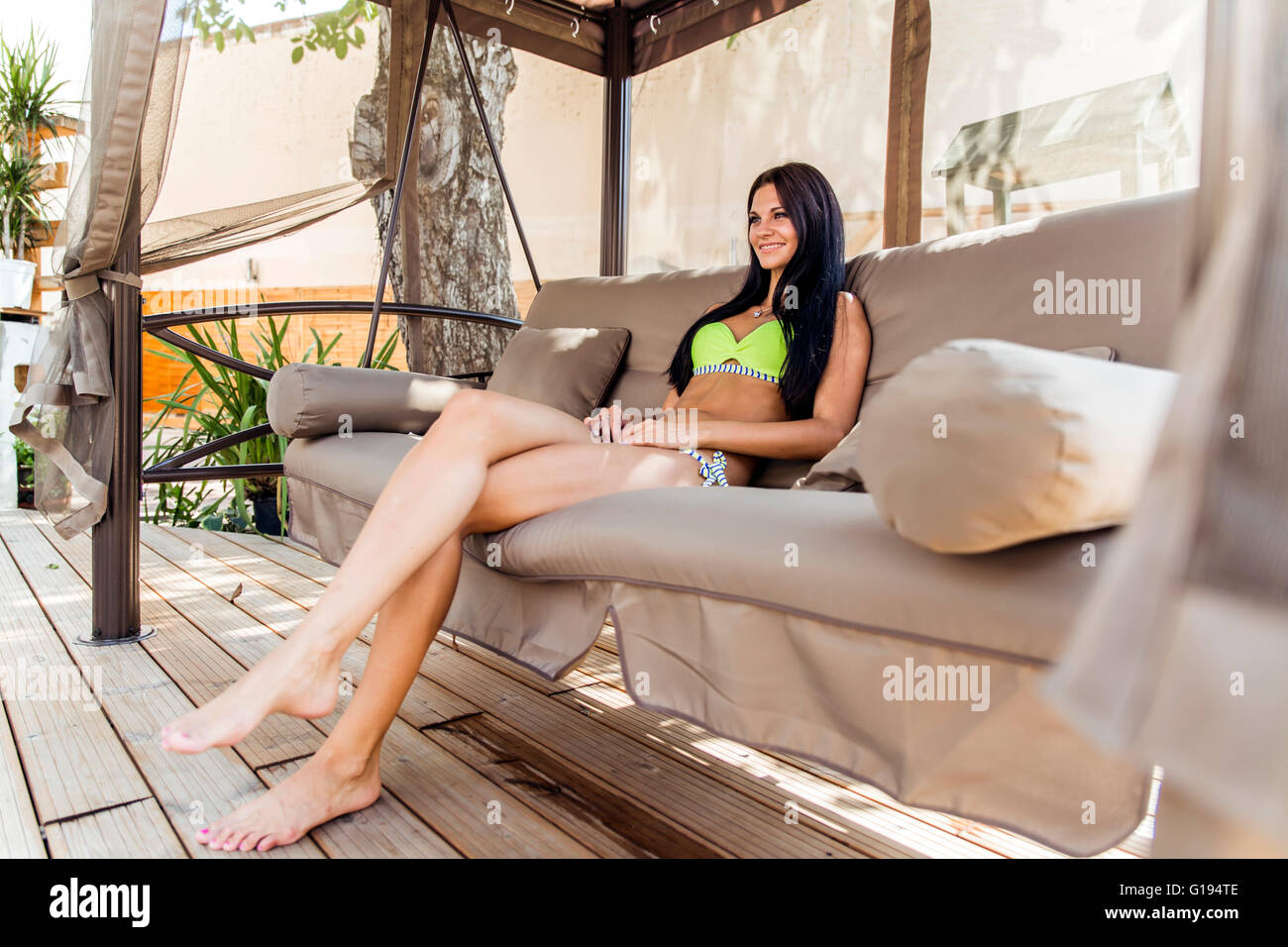Beautiful young lady shading herself from sun in a big swing and relaxing - Stock Image