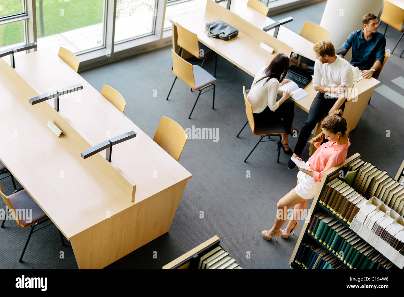 Group of students studying in a library and educating themselves - Stock Image