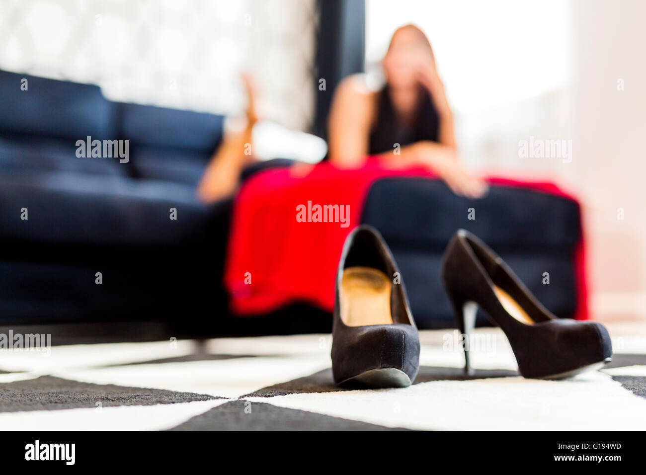 Closeup of high heels shoes in a hotel room and a woman in the background - Stock Image