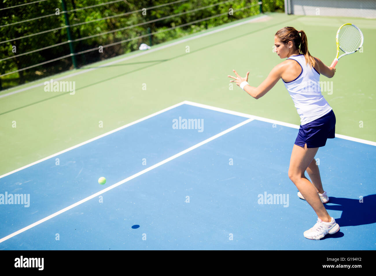 Beautiful female tennis player in action, hitting a forehand Stock Photo