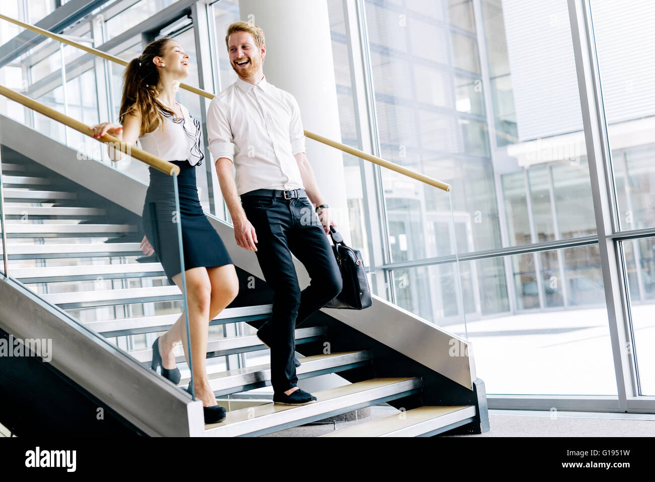 Business colleagues talking on stairs and flirting while smiling - Stock Image