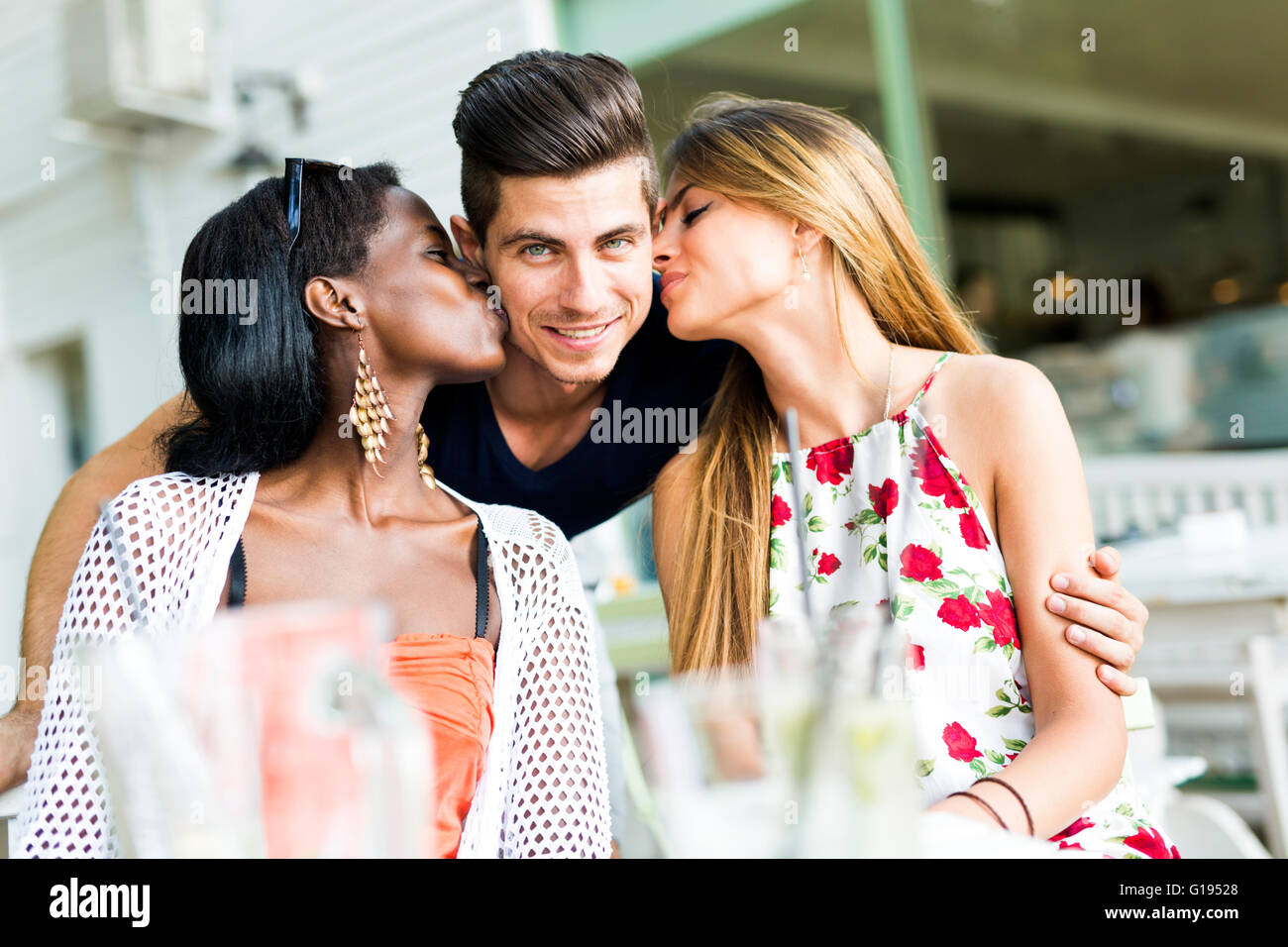 Happy young friends smiling outdoors being close to each other on a summer day Stock Photo