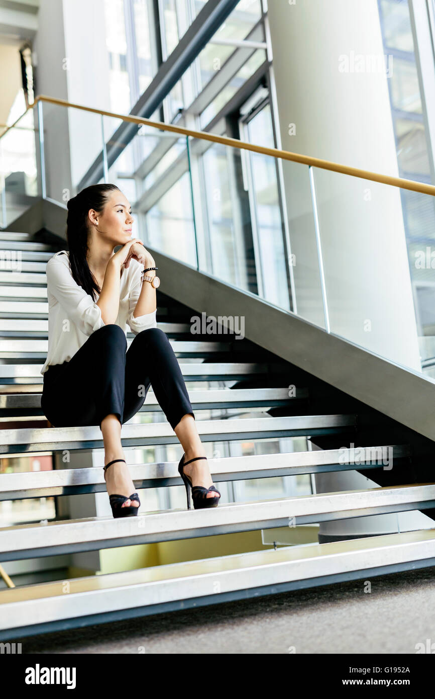 Businesswoman sitting on stairs and thinking. Fashion style photo - Stock Image