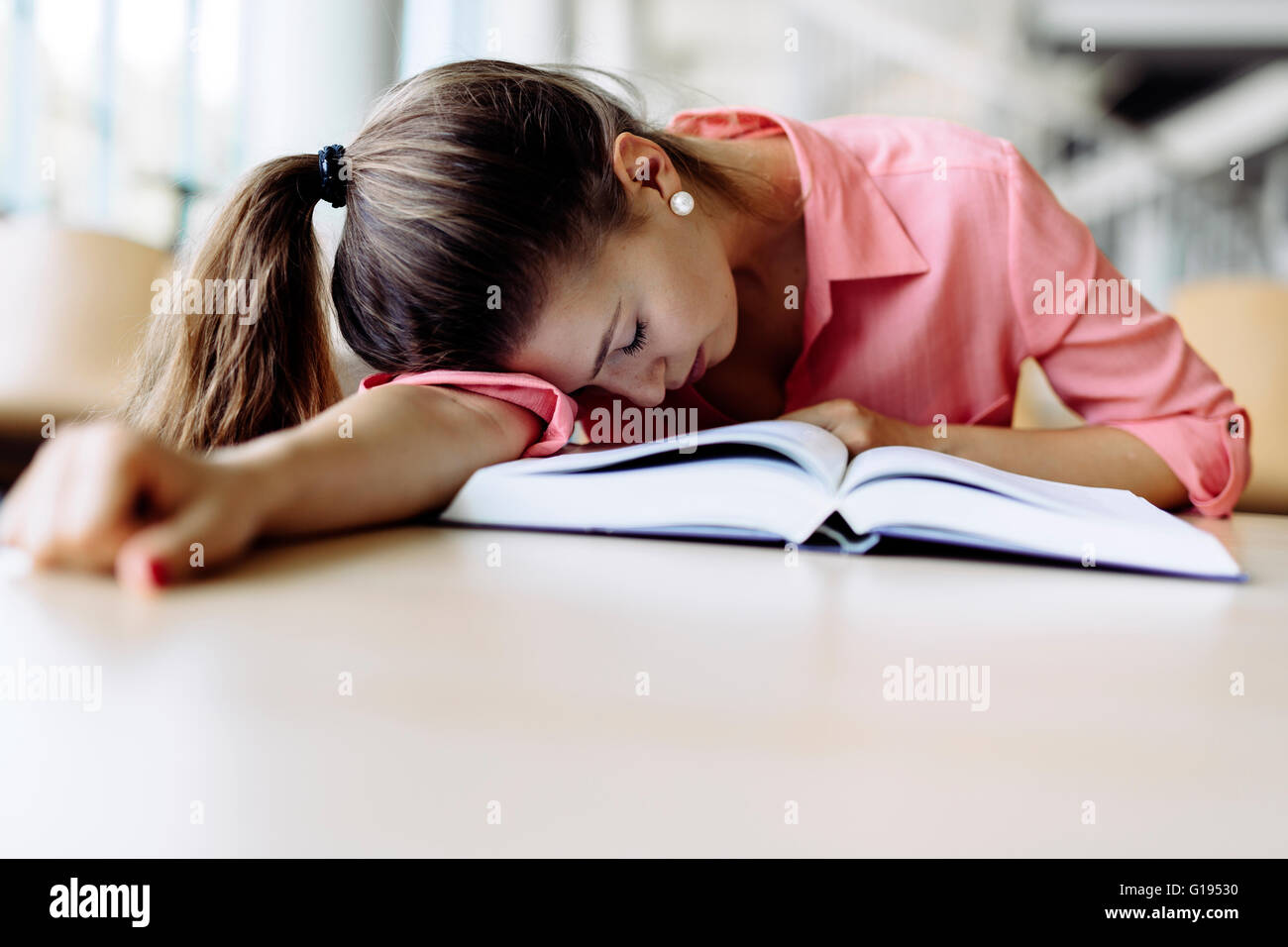 Beautiful pretty woman fallen asleep on the table while studying and reading a book - Stock Image