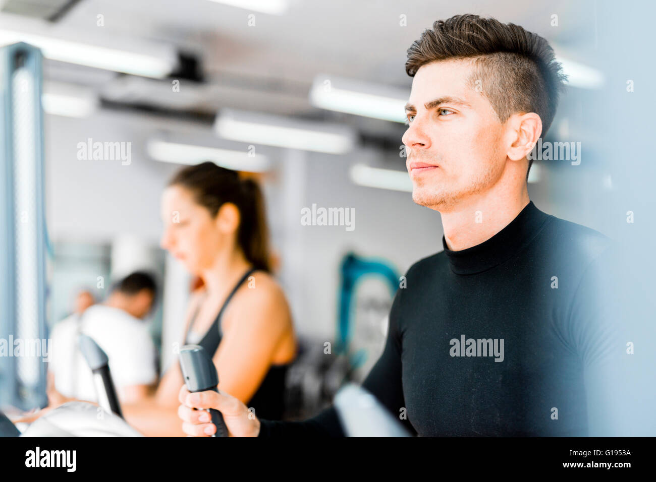 Group of healthy young people using treadmill and elliptical trainer in a gym - Stock Image