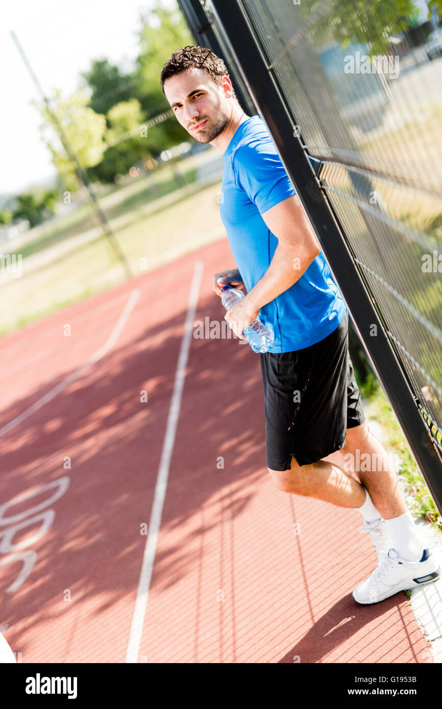 Young athlete taking a break from exercising on a hot summer day - Stock Image