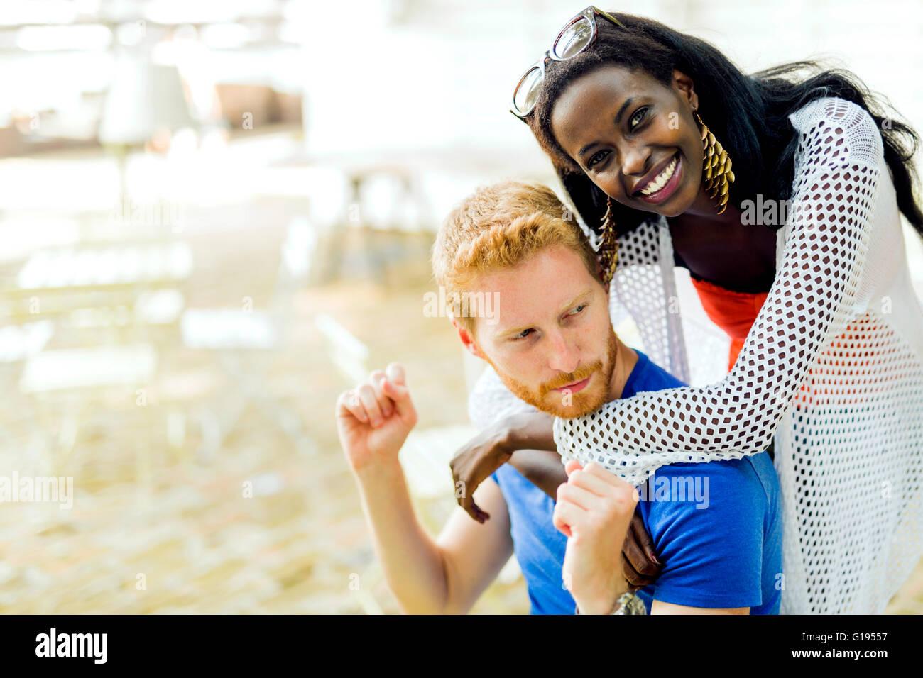 Beautiful black woman hugging ginger boyfriend and smiling - Stock Image
