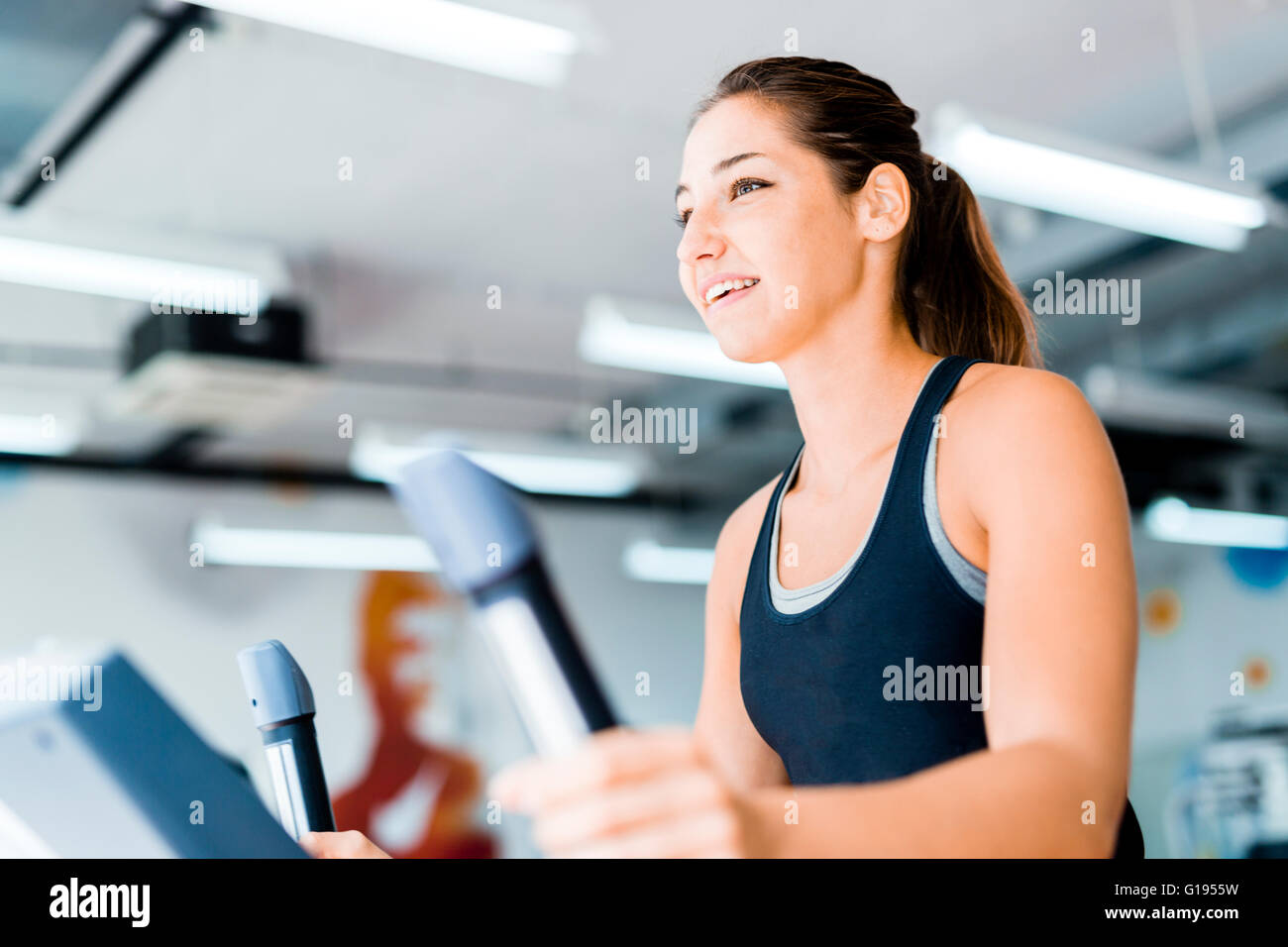 Beautiful young lady using the elliptical trainer in a gym in a positive mood - Stock Image