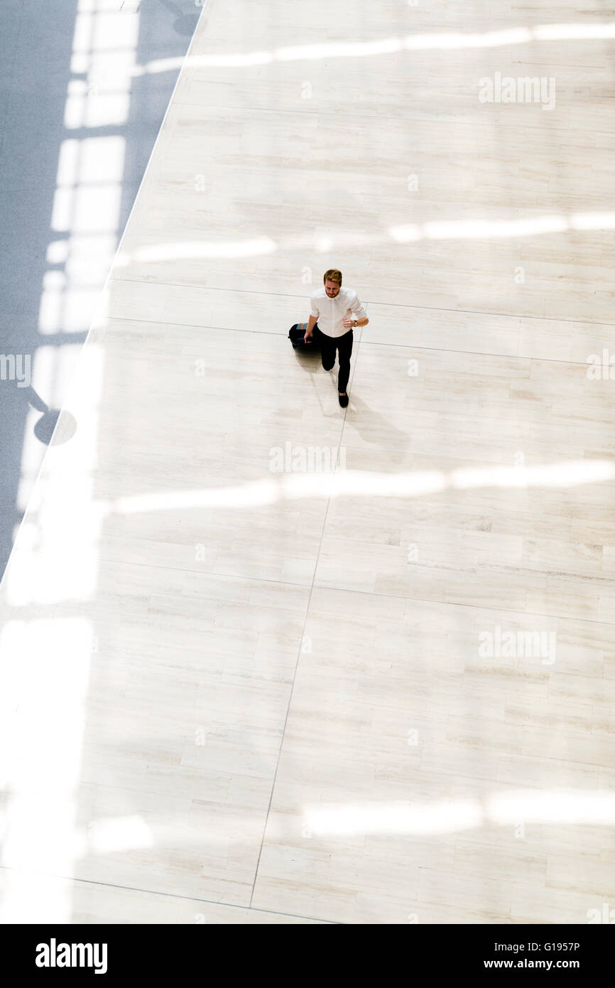 Handsome business holding a trolley and walking in a modern building seen from above - Stock Image