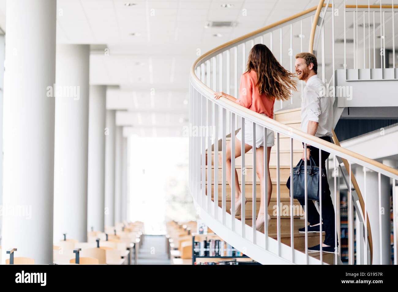 Beautiful businesswoman handsome businessman climbing stairs in a beautiful environment - Stock Image