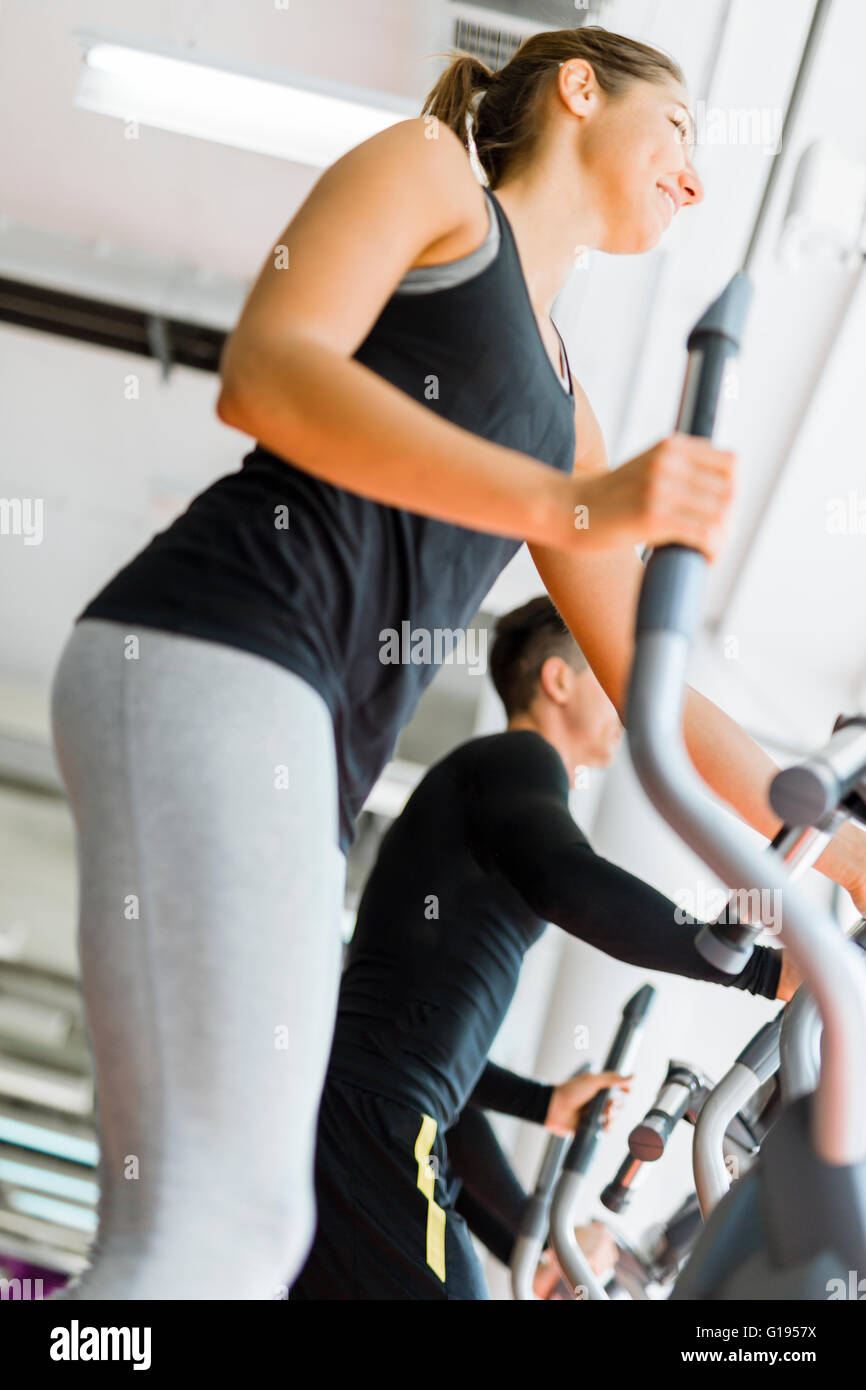 Beautiful fit young woman working out on a stepper together with her friends - Stock Image