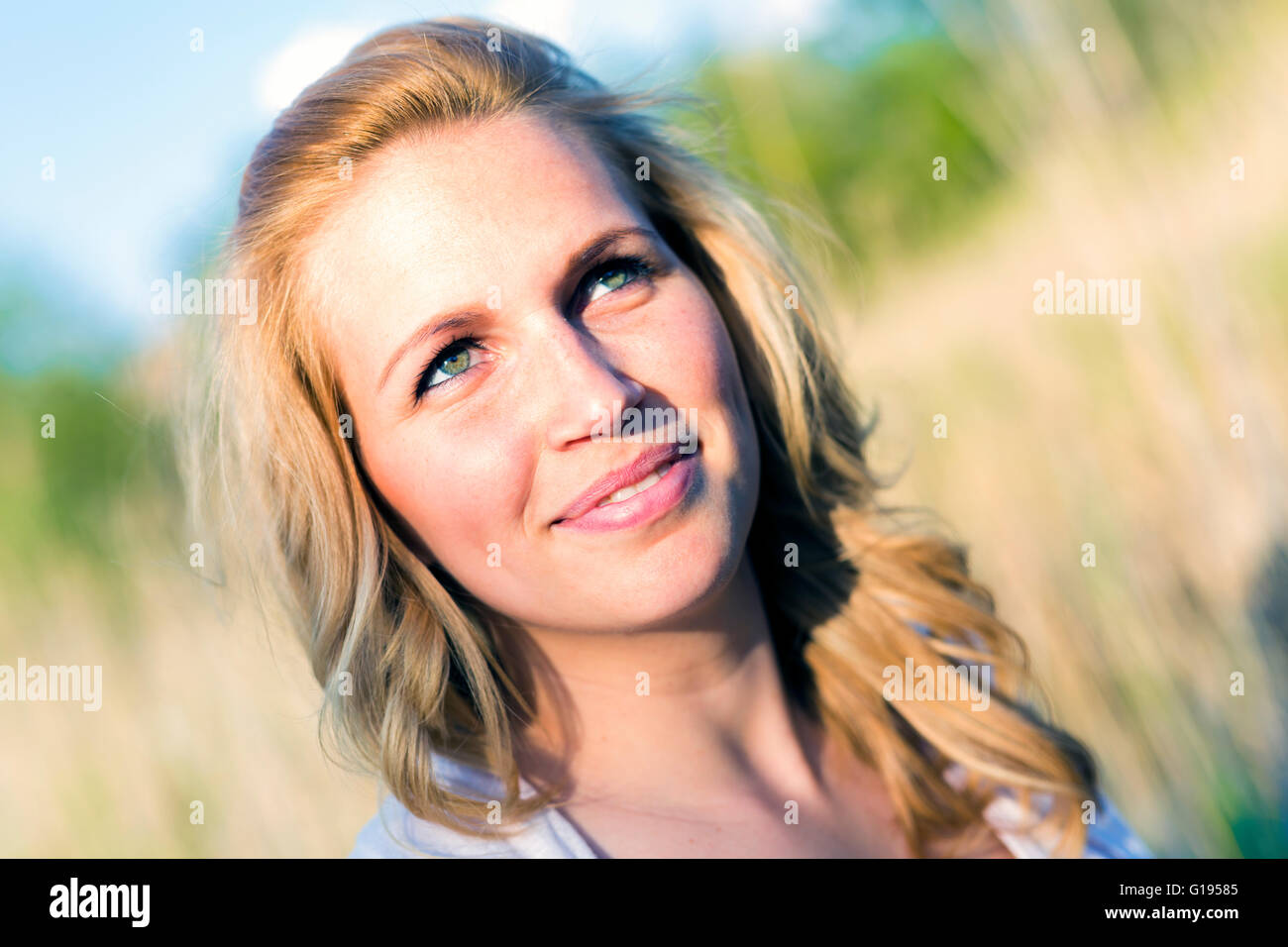 Portrait of a beautiful smiling woman in nature / outdoors - Stock Image