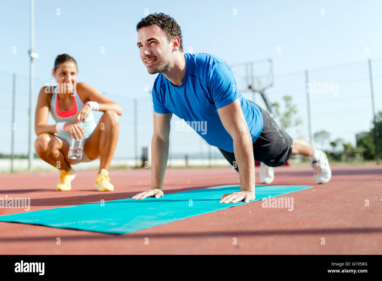 Young, beautiful, fit and healthy personal trainer counting push-ups and motivating - Stock Image