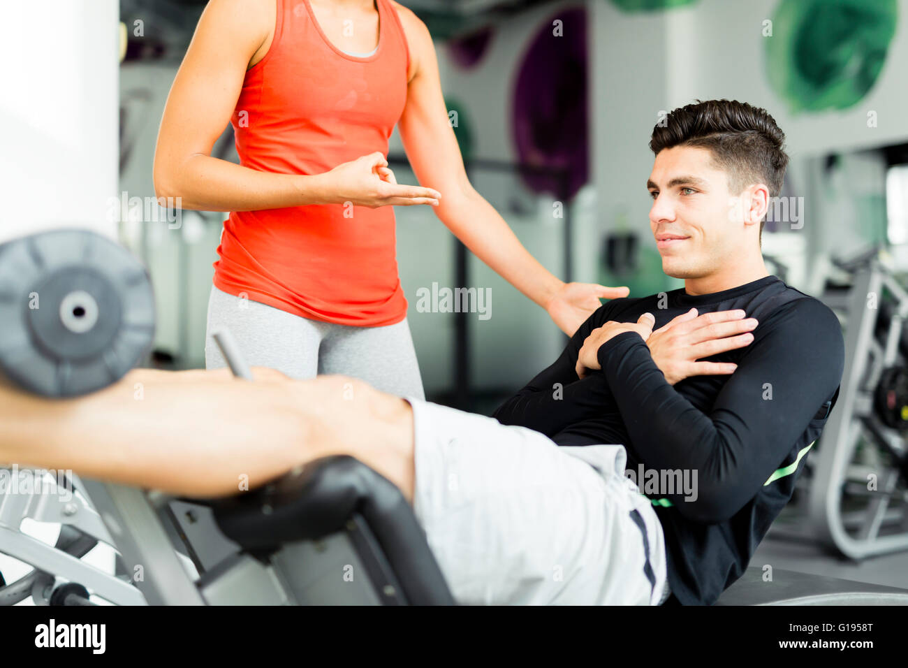 Beautiful young woman instructing a young man in the gym and overlooking his workout - Stock Image