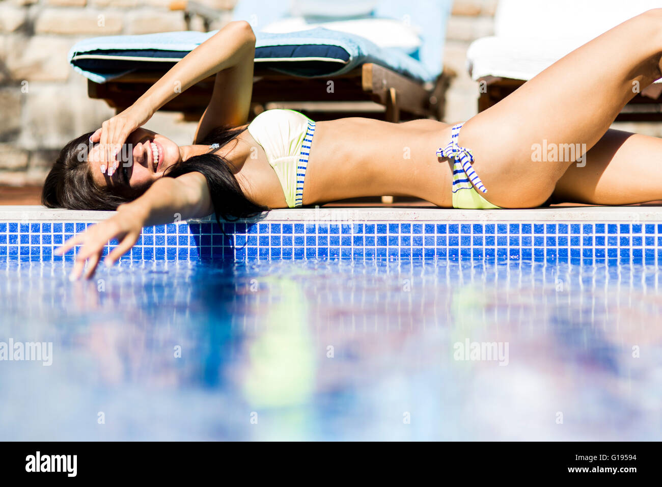 Beautiful young woman sunbathing at the poolside during summer - Stock Image