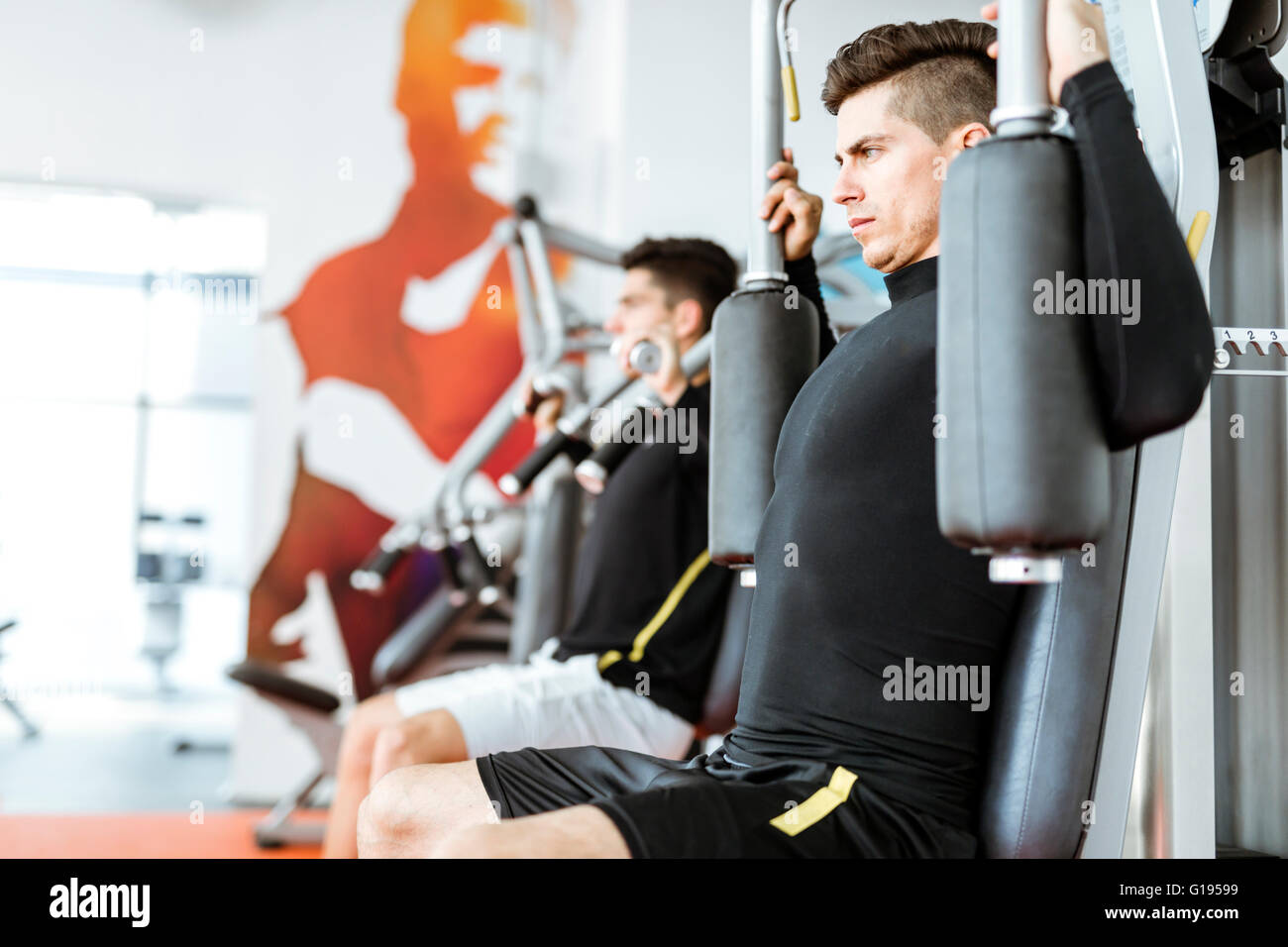 Two handsome men working out in a beautiful fitness center - Stock Image