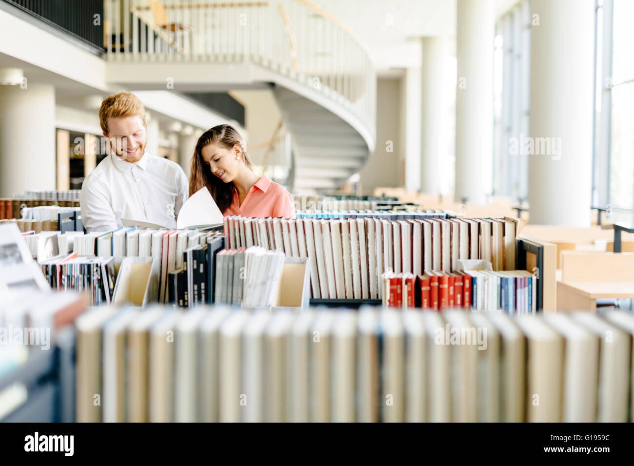 Two  smart students reading and studying in library whole searching through books on the shelves - Stock Image