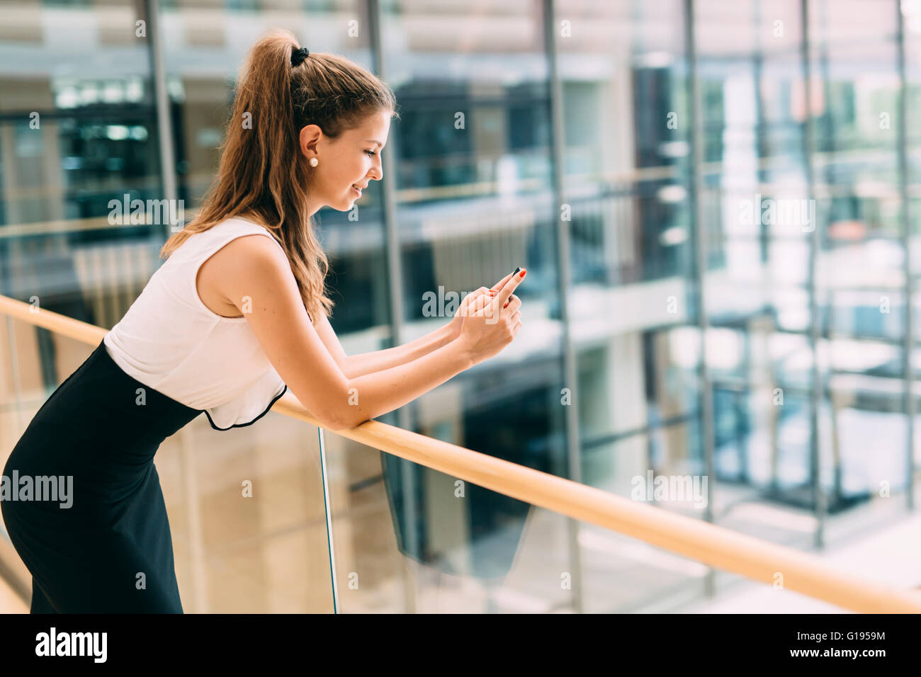 Beautiful businesswoman using phone and smiling - Stock Image