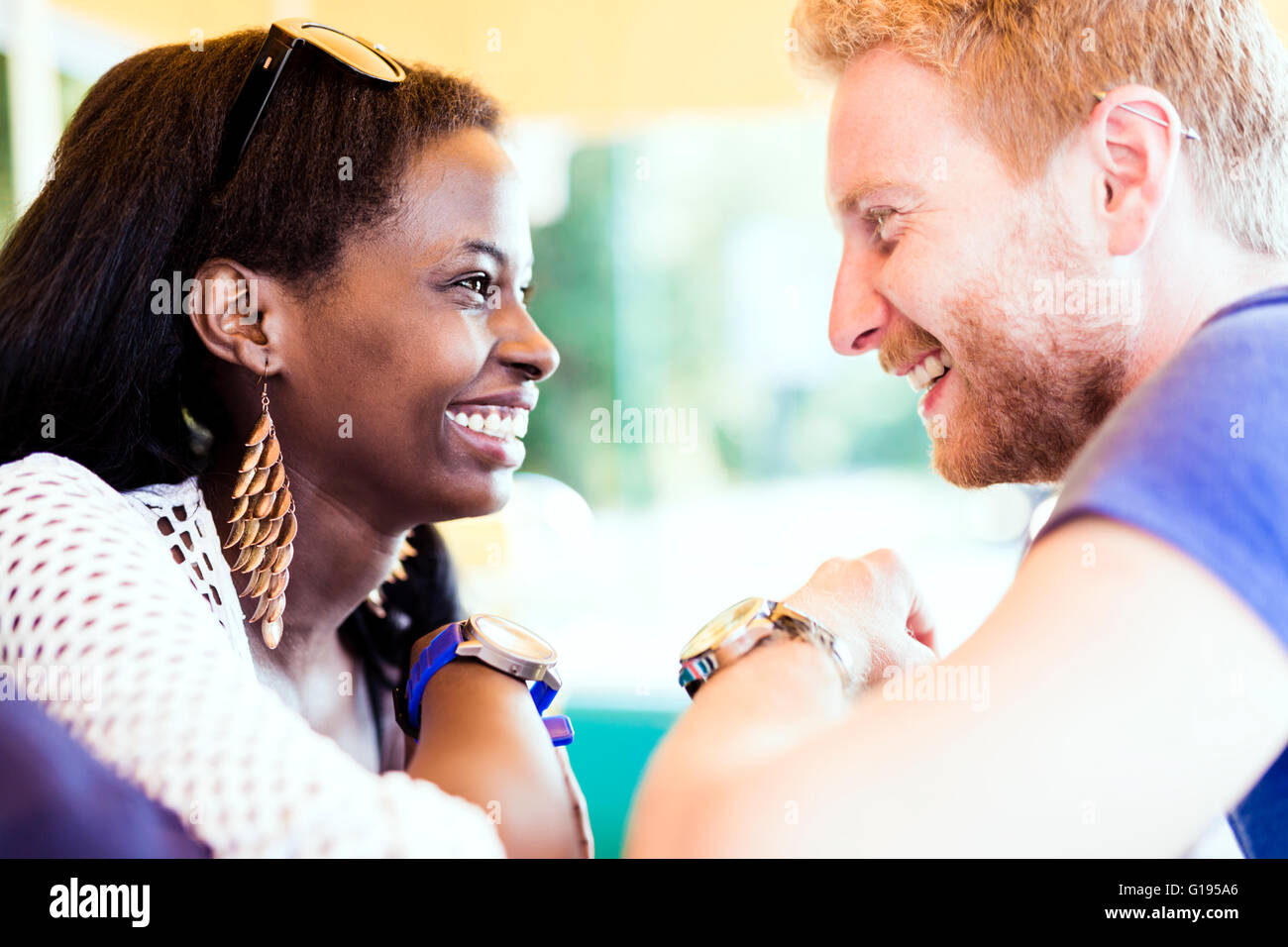 Romantic couple smiling while looking into each others eyes with love - Stock Image