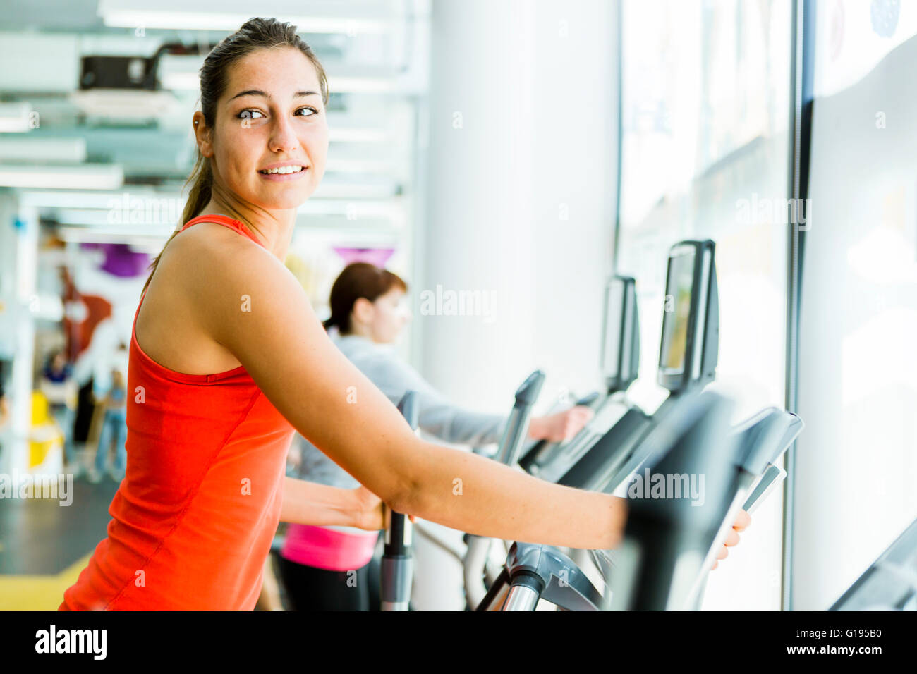 Young fit woman using an elliptic trainer in a fitness center and smiling - Stock Image