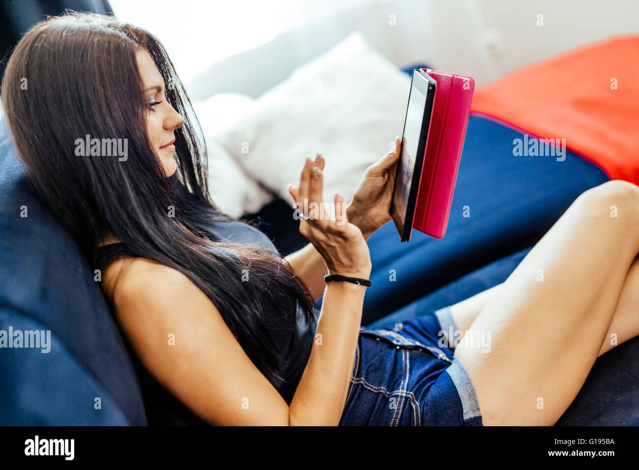 Beautiful happy young woman using a tablet - Stock Image