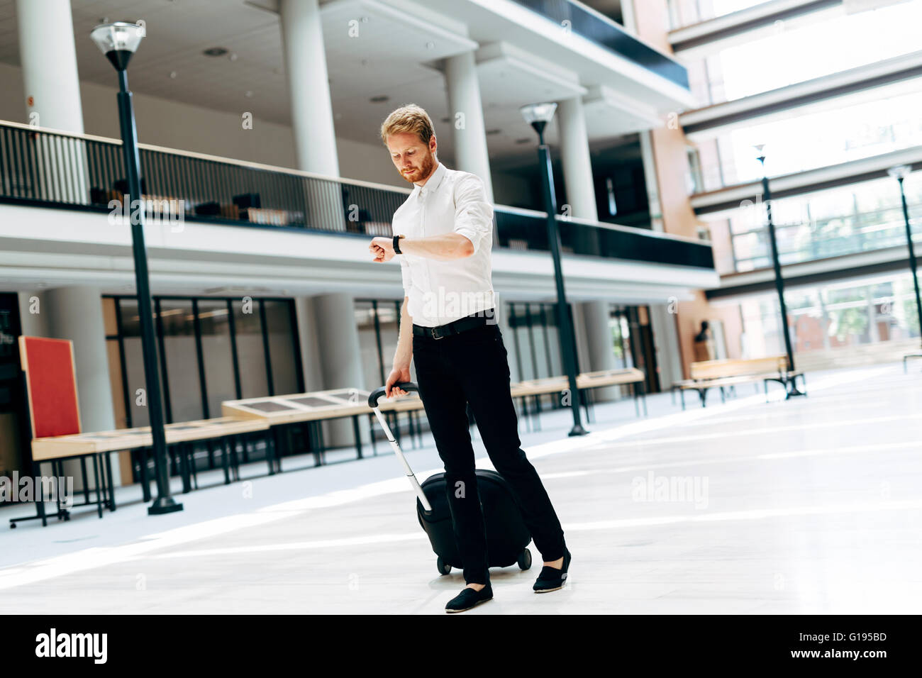 Handsome business holding a trolley and walking in a modern building - Stock Image