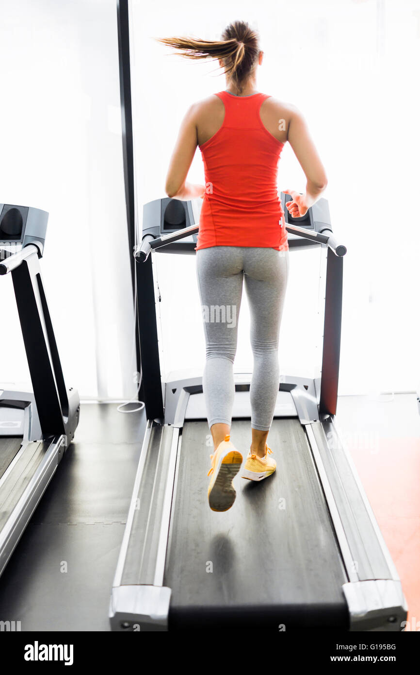 Beautiful young woman running on a treadmill in fitness center - Stock Image