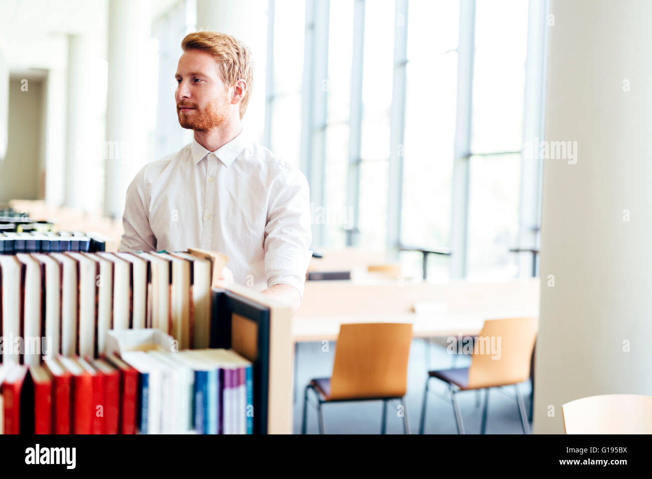 Handsome student searching for a book in a beautiful library - Stock Image