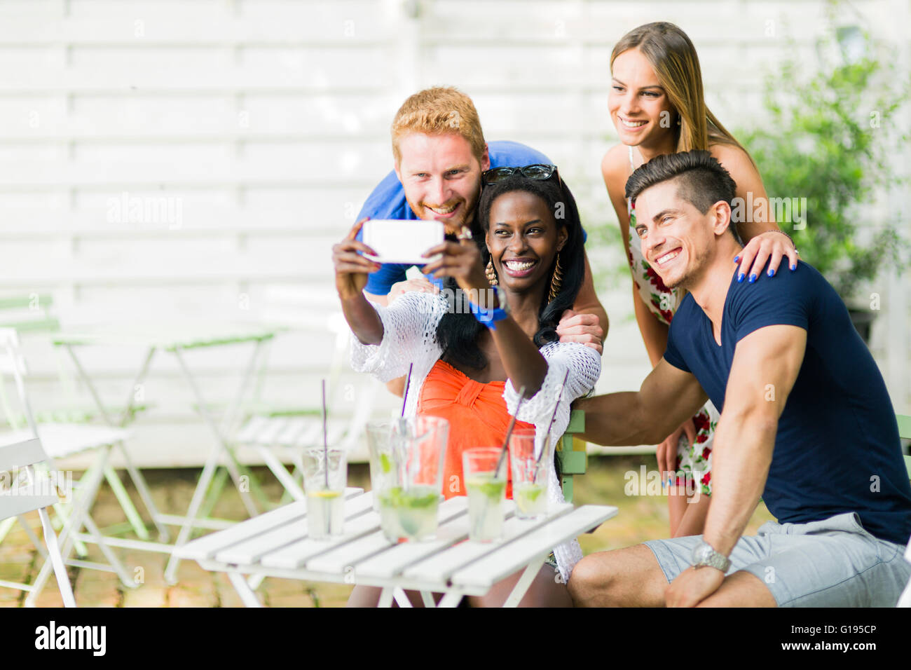 A group of friends sitting a table and talking smiling  while taking selfies on a hot summer day - Stock Image