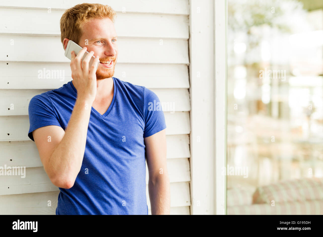 Happy red haired handsome man using phone and smiling during a summer day - Stock Image